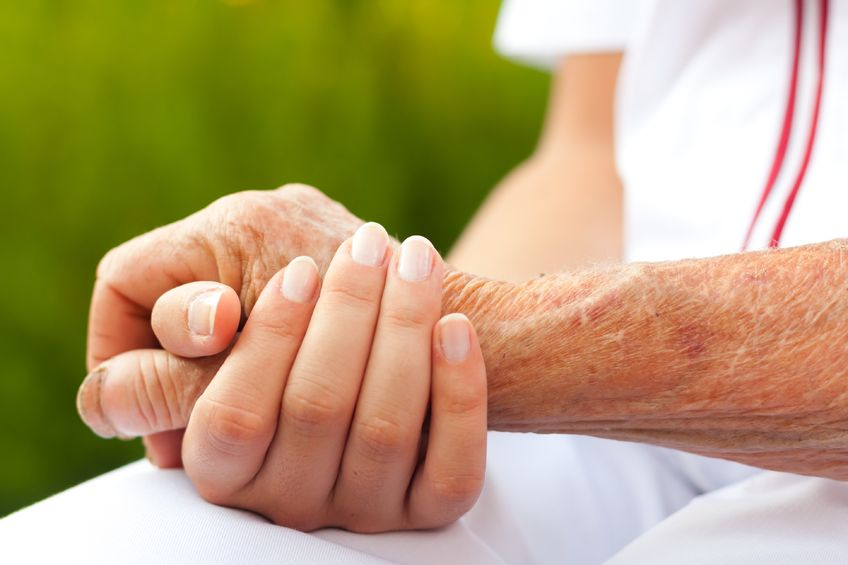 doctor holding hand of an elderly person